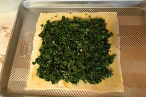 Spread the cooked kale/other greens on the mustard-spread pastry dough.